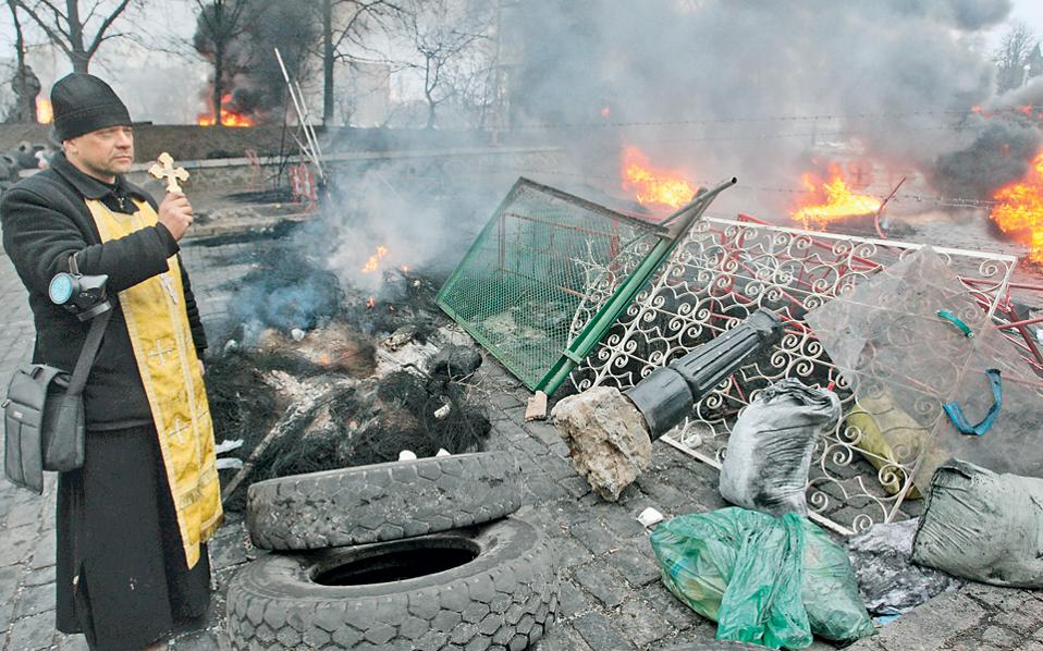 Ουκρανός ιερέας, με τον σταυρό στο χέρι, στέκεται σε οδόφραγμα μετά τις βίαιες συγκρούσεις διαδηλωτών και αστυνομίας στο Κίεβο την περασμένη Πέμπτη.